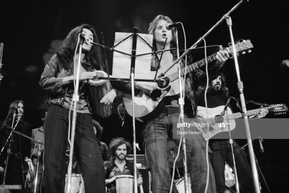 Married singer musicians Yoko Ono and John Lennon (1940 - 1980) perform at the 'Free John Now' rally at Crisler Arena , Ann Arbor, Michigan, December 10, 1971. Political activist Jerry Rubin (1938 - 1998) (center, rear) plays bongos with them. The rally was in support of imprisoned White Panther leader John Sinclair. (Photo by David Fenton/Getty Images)